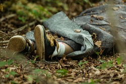 Close up view of legs of dead body wrapped in plastic fabric thrown in woods covered with leaves
