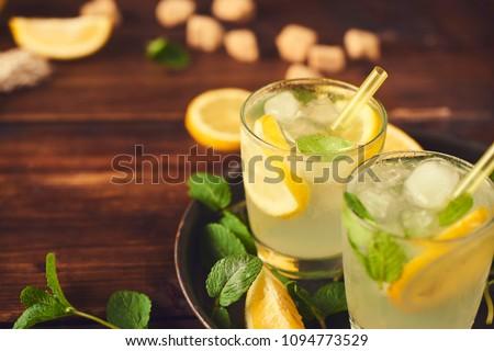 Close up view of lemonade in glass. Preparing of lemonade. ingredients for lemonade on rustic wooden table