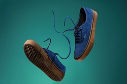 Close up view of levitation blue sneakers shoes with  flying laces over green background with copy space for text.