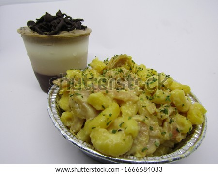 Close up view of macaroni schotel mac n cheese with elbow macaroni pasta cheesy cream, sausage beef meat cornet with a cup glass dessert of cold sweet  pudding chocolate milky white vanilla brown  Foto stock ©
