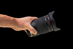 Close up view of male hand holding camera lens isolated on black background.