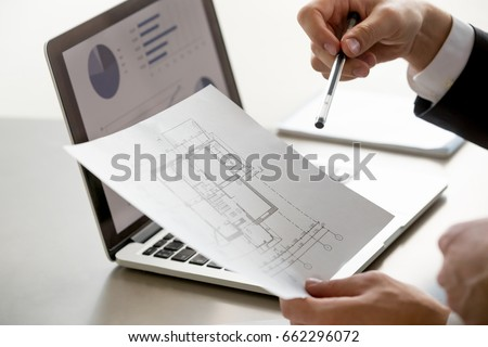 Close up view of male hand holding project plan, financial statistics data on laptop screen at background, analyzing real estate market, mortgage loan with low rate, construction investment