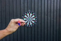 Close up view of male hand throwing missile of dartboard. Sport concept. Sweden.