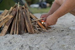 Close up view of male hands holding matches near the firewoods. Man making fire outdoors.