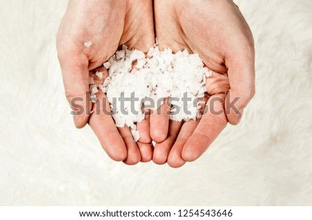 Close up view of man hands holding Magnesium Chloride vitamin salt flakes in palms hands, isolated on white soft fur background. Ingredient for making feet bath with Magnesium salt flakes.