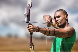 Close up view of man practicing archery against landscape of countryside