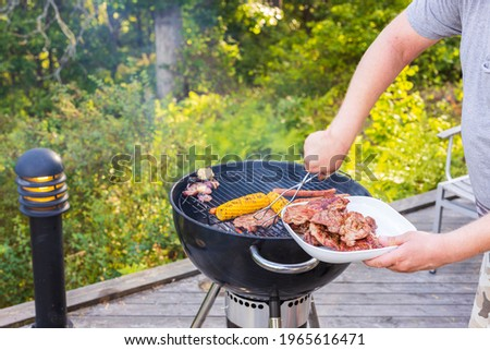Close up view of man's hands grilling food on coal grill. Sweden. Stock fotó ©