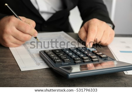 Close up view of man sitting at table with calculator, document and pen. Taxation concept