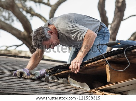 Close up view of man using removing rotten wood from leaky roof. After removing fascia boards he has discovered that the leak has extended into the beams and decking.