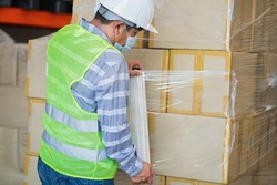 close up view of man worker wearing protective face mask and safety suite wrapping stretch film parcel on pallet in factory warehouse, logistic industry concept.
