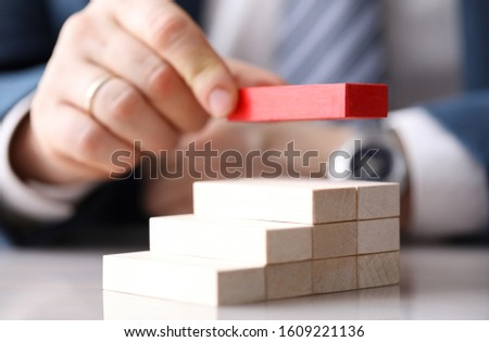 Close-up view of mans hand putting red unique brick on top of light wooden blocks. Metaphor to management and authority. Leadership ideas and uniqueness concept