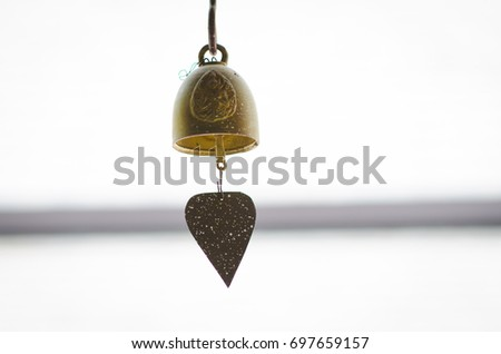 Close up view of many beautiful old fashioned golden bells heart buddha hanging as pray new year. #697659157