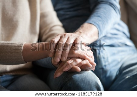 Close up view of mature couple holding hands, loving caring elderly man supporting senior middle aged woman giving psychological empathy and understanding in marriage, getting older together concept