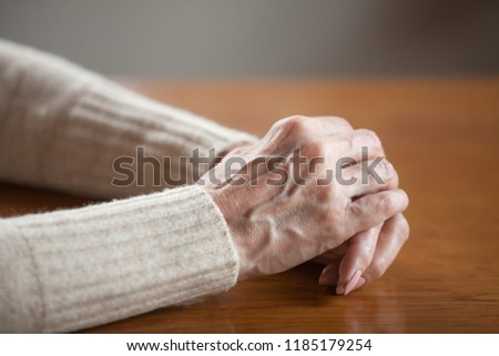 Close up view of mature old female person wrinkled hands with veins on table, middle aged senior elderly woman holding arms folded praying as concept of aging process, healthcare, loneliness or grief #1185179254