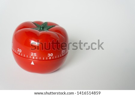 Close up view of mechanical tomato shaped kitchen clock timer for cooking and studying. Used for pomodoro technique for time & productivity management. Isolated on white background, set at 25 minutes. #1416514859