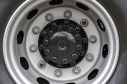 Close up view of metal bolt on new wheel. Concept of maintenance agrarian machinery. Replace and fixing locking hubs