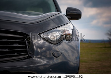 Close up view of modern luxury black car xenon lamp headlight. Beautiful sky reflection, carbon front grill, modern and prestigious SUV  #1390901192