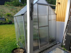 Close up view of of greenhouse on backyard. Gardening concept.