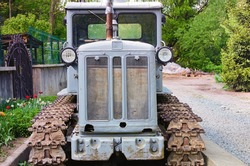 Close-up view of old crawler tractor. Detailed view of tractor. Soviet gray crawler. Nature landscape background. Front-bottom view.