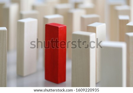 Close-up view of one different red cube among other identical wooden blocks. Business organization and individuality, leadership and uniqueness concept