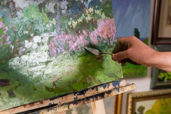 Close up view of painter's hand holding a palette knife ending his picture of a garden scene with flowers and trees