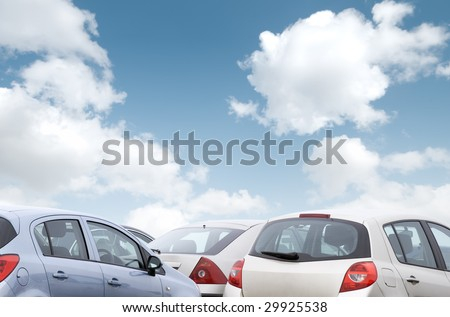Close-up view of parked cars with cloudy blue sky
