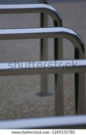 Close up view of pattern of curved inox tubes used to place bikes in a french city. Abstract urban image with curving lines. Metallic lighted objects with vertical and horizontal shapes.   #1269535780