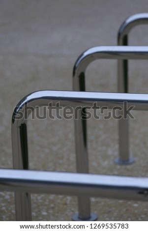Close up view of pattern of curved inox tubes used to place bikes in a french city. Abstract urban image with curving lines. Metallic lighted objects with vertical and horizontal shapes.   #1269535783