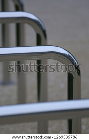 Close up view of pattern of curved inox tubes used to place bikes in a french city. Abstract urban image with curving lines. Metallic lighted objects with vertical and horizontal shapes.   #1269535786