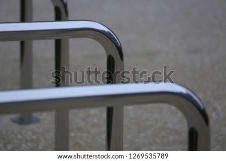 Close up view of pattern of curved inox tubes used to place bikes in a french city. Abstract urban image with curving lines. Metallic lighted objects with vertical and horizontal shapes.   #1269535789