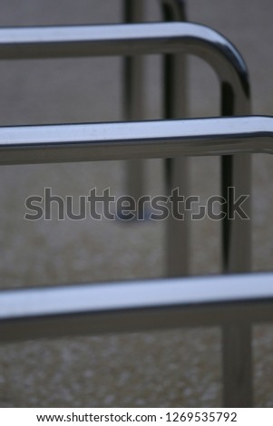 Close up view of pattern of curved inox tubes used to place bikes in a french city. Abstract urban image with curving lines. Metallic lighted objects with vertical and horizontal shapes.   #1269535792