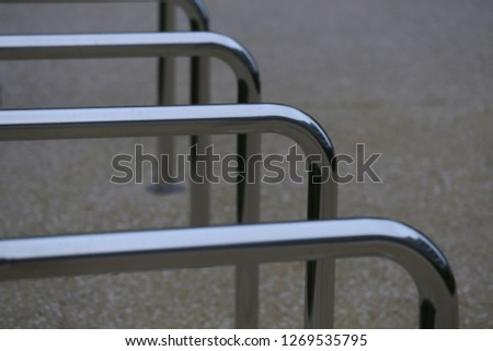 Close up view of pattern of curved inox tubes used to place bikes in a french city. Abstract urban image with curving lines. Metallic lighted objects with vertical and horizontal shapes.   #1269535795