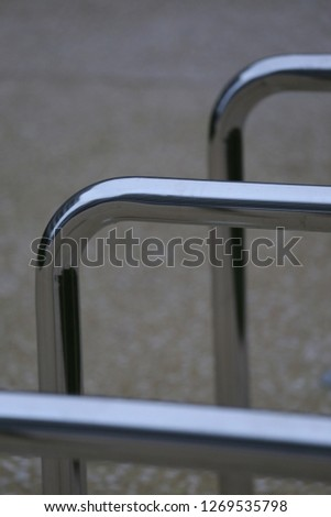 Close up view of pattern of curved inox tubes used to place bikes in a french city. Abstract urban image with curving lines. Metallic lighted objects with vertical and horizontal shapes.   #1269535798