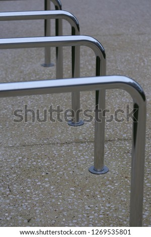 Close up view of pattern of curved inox tubes used to place bikes in a french city. Abstract urban image with curving lines. Metallic lighted objects with vertical and horizontal shapes.   #1269535801