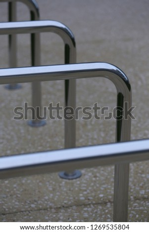 Close up view of pattern of curved inox tubes used to place bikes in a french city. Abstract urban image with curving lines. Metallic lighted objects with vertical and horizontal shapes.   #1269535804
