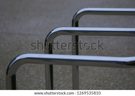 Close up view of pattern of curved inox tubes used to place bikes in a french city. Abstract urban image with curving lines. Metallic lighted objects with vertical and horizontal shapes.   #1269535810