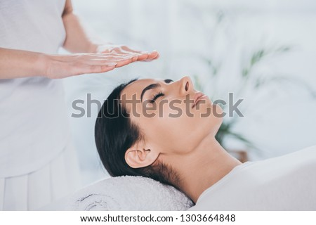 close-up view of peaceful young woman with closed eyes receiving reiki treatment