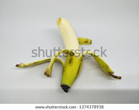 Close up view of peels off one yellow banana peel isolated on white background. Organic local tropical fruit healthy for daily consume with brown spots on the skin. Peeling into four side. Big fresh #1374378938