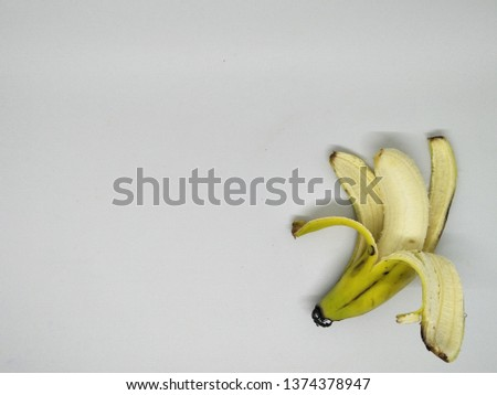 Close up view of peels off one yellow banana peel isolated on white background. Organic local tropical fruit healthy for daily consume with brown spots on the skin. Peeling into four side. Big fresh #1374378947