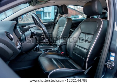 Close up view of perforated black leather car interior. Manual transmission, electric memory seats, heated and ventilated seats, panoramic roof. Interior detail. Modern car, comfortable seats.