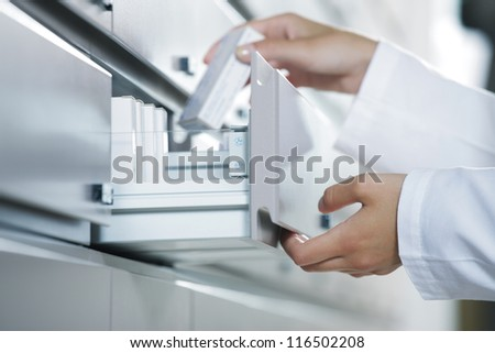 Close up view of pharmacist taking medicine from drawer