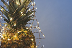 Close up view of pineapple with Christmas light garland with copy space, greeting card concept on gray background
