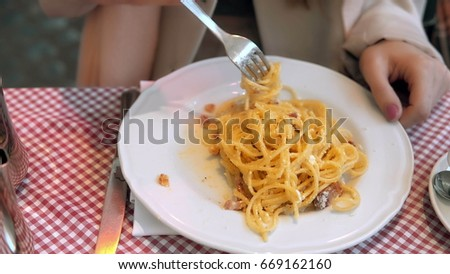 Stock Photo Close-up view of plate with spaghetti. Young happy woman sitting in cafe ang eating pasta after long busy day.