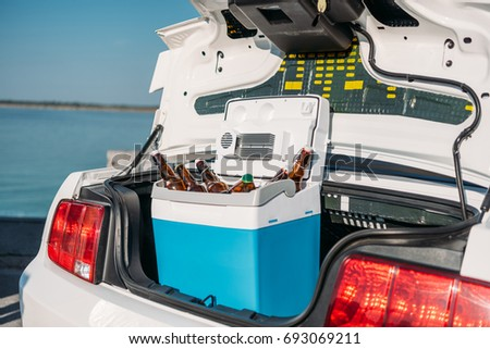 close up view of portable fridge with beer standing in car #693069211