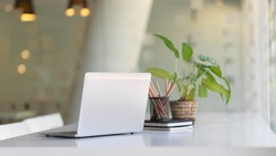 Close up view of portable workspace with laptop, stationery and plant pot o the table in co-working space