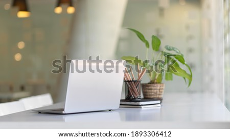 Close up view of portable workspace with laptop, stationery and plant pot o the table in co-working space ストックフォト ©