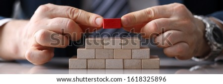 Close-up view of presentable man putting unique red block on staircase of other identical bricks. Pyramid of wooden cubes on desktop. Authority and uniqueness concept