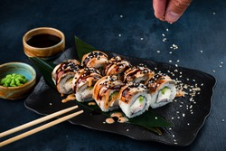 Close-up view of process of preparing rolling sushi. making the sushi with sauce and sesame seeds, pours delicious fresh rolls with a sauce. Dark background