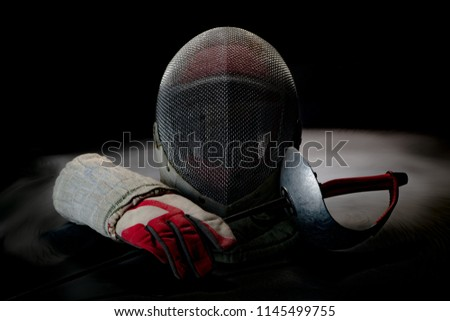 Close-up view of Professional fencing protective equipment for sabre have a fencing old mask, fencing old glove and old rapier on black background in the smoke