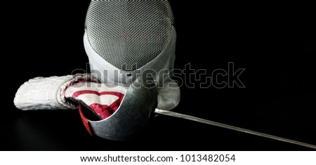 Close-up view of Professional fencing protective equipment for sabre is, fencing mask, fencing glove and rapier on black background